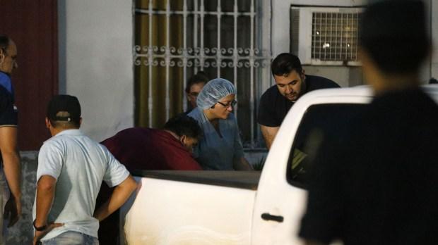 Empleados y policía carga los restos de Fehr a una camioneta (AP Photo/Jorge Saenz)