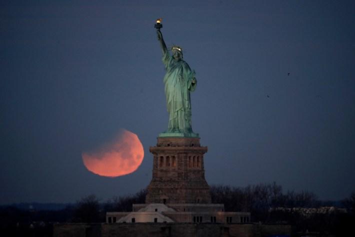 La superluna se pone sobre la Estatua de la Libertad en Nueva York