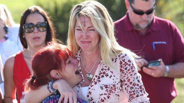 Desconsoladas, una madre y su hija lloran en las afueras de Marjory Stoneman Douglas. (AP)