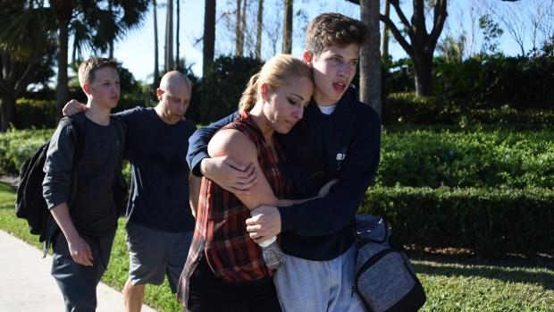 Dos hermanos se dirigen a su casa junto a sus padres tras el tiroteo. (AFP)
