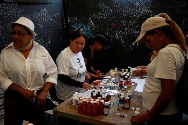 Voluntarios reparten medicamentos durante el acto de campaña en Valencia (REUTERS/Carlos Jasso)