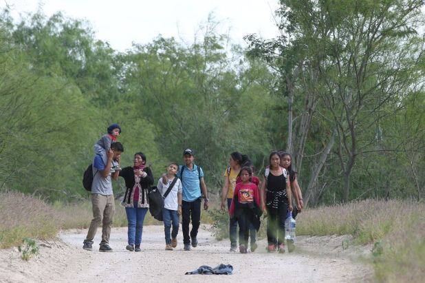 Migrantes caminan en un camino de tierra cerca de la frontera estadounidense en McAllen (Texas) (Loren Elliott/Reuters)
