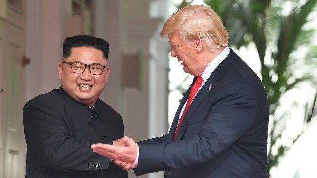 Kim Jong-un saluda sonriente al presidente estadounidense. (AFP)