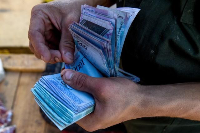 Un hombre cuenta los billetes de mil bolívares para comprar fruta y verdura en el mercado de Coche, en Caracas . El FMI proyecta la inflación en 13.800% para 2018 (AFP / Federico PARRA)