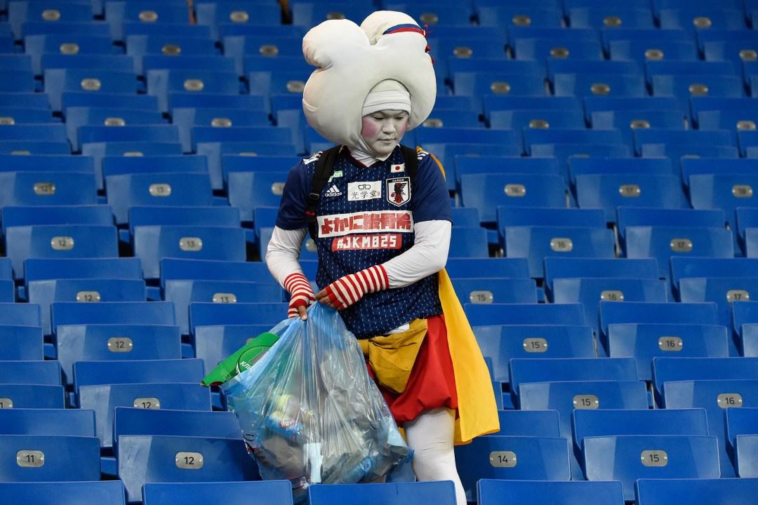 Un fanático japonés da el ejemplo y recolecta los resiudos después de la derrota de su país ante Bélgica en los octavos de final