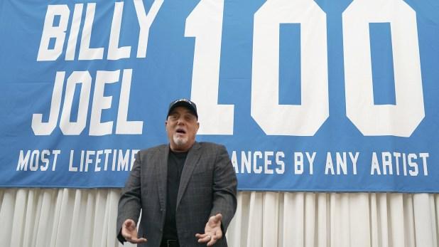 Billy Joel junto a la banderola celebrando la actuación 100 (AFP)