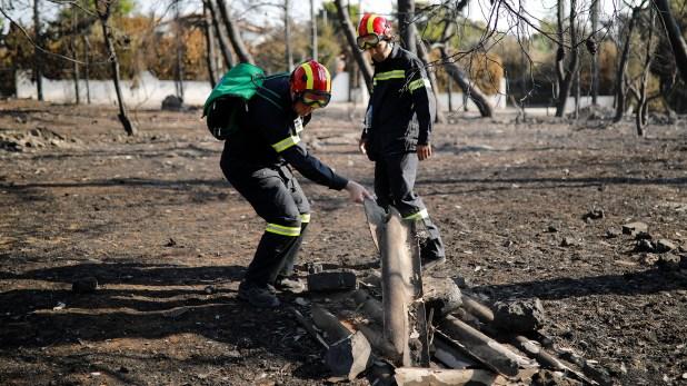 Dos bomberos observan lo que se quemó (Reuters)