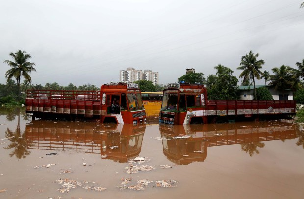 Dos camiones parcialmente sumergidos en el agua (REUTERS/Sivaram V TPX IMAGES OF THE DAY)