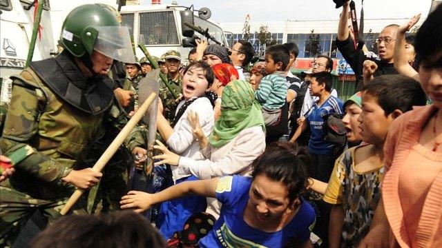Mujeres étnicas uigur chocan con la policía antidisturbios china cuando protestan en Urumqi, en el extremo oeste de la provincia de Xinjiang (AFP)