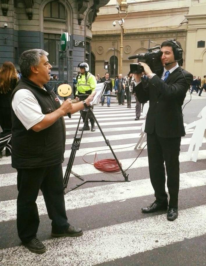 Cámara en mano, Nicolás Feuermann bromea con un compañero de C5N en medio de una cobertura