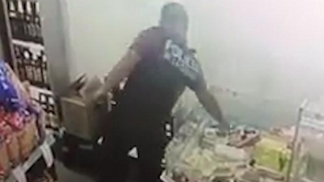 Imagen de la cámara de seguridad del supermercado chino: el policía elige y se lo lleva