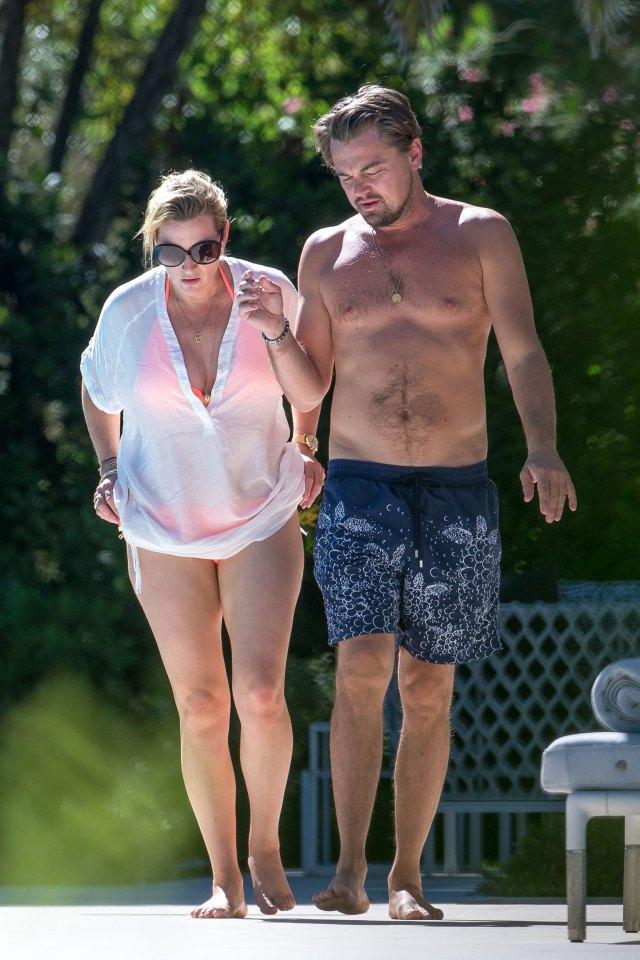 Leonardo Di Caprio camina en la playa con un bañador azul con estampa blanca, junto a su amiga y colega, Kate Winslet (The Grosby Group)
