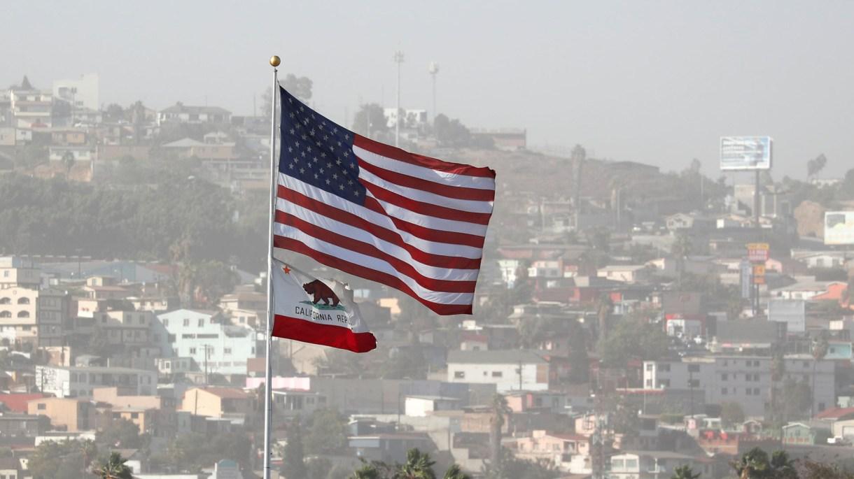 La bandera de Estados Unidos y la de California en la frontera con México. (REUTERS/Mike Blake)