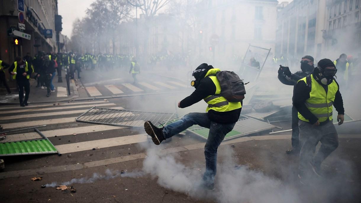 Una manifestante equipado con una máscara de gas patea una bomba de gas lacrimógeno(AFP)