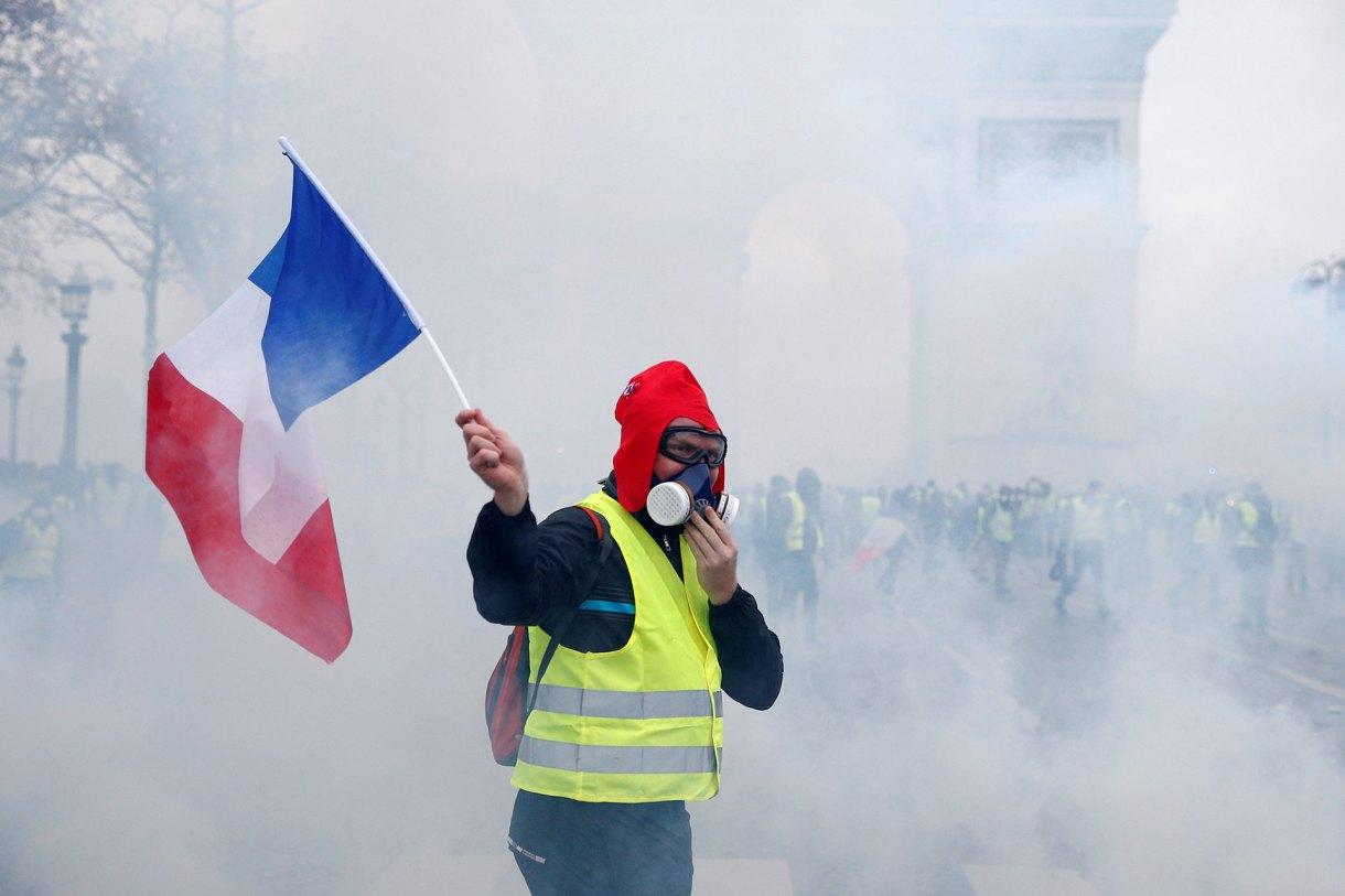 """En medio de los disturbios, un """"chaleco amarillo"""" agita una bandera francesa protegido con una máscara antigás (Reuters)"""