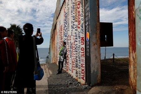 Turistas chinos aprovechan su estancia en la frontera para fotografiarse en la valla que divide México de EEUU. (Foto: Reuters)