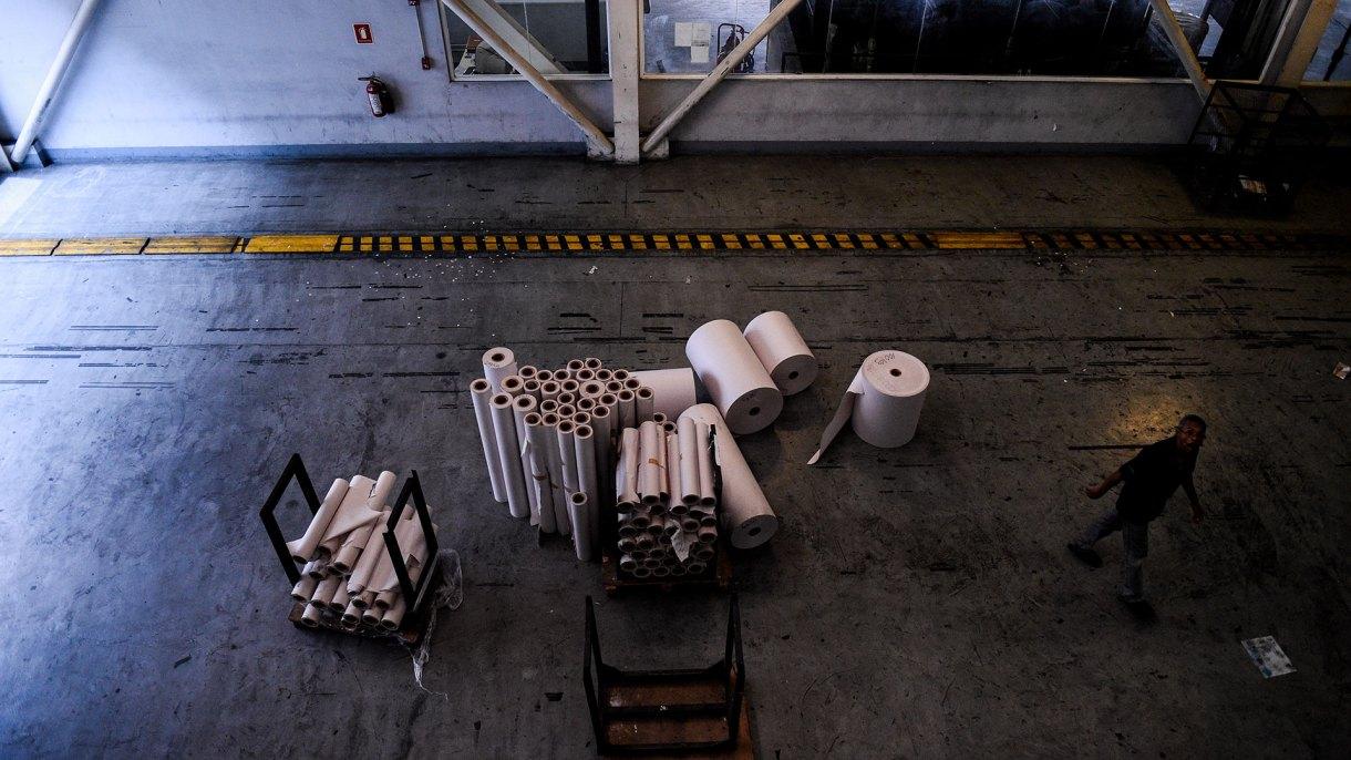 En esta foto de archivo tomada el 6 de octubre de 2018, un empleado camina junto a los rollos de papel restantes en la sala de impresión del periódico venezolano El Nacional (AFP)