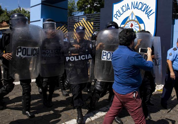 Agentes de la policía nacional repliegan al periodista Wilfedo Miranda del semanario Confidencial al llegar a la sede central de la policía a pedir explicaciones sobre el allanamiento del medio de comunicación. (EFE/Jorge Torre)