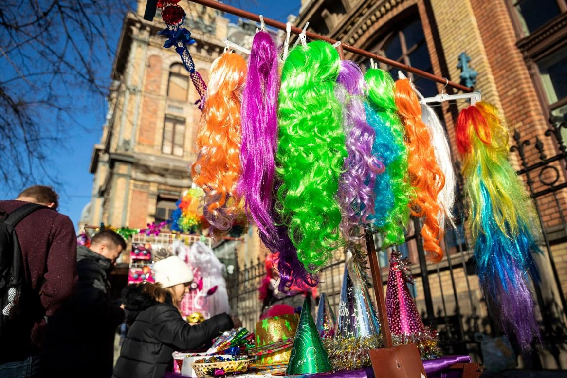Los clientes compran adornos divertidos, pelucas de colores y trompetas de papel para celebrar la Nochevieja frente a la estación de tren Nyugati (Oeste) en Budapest, Hungría