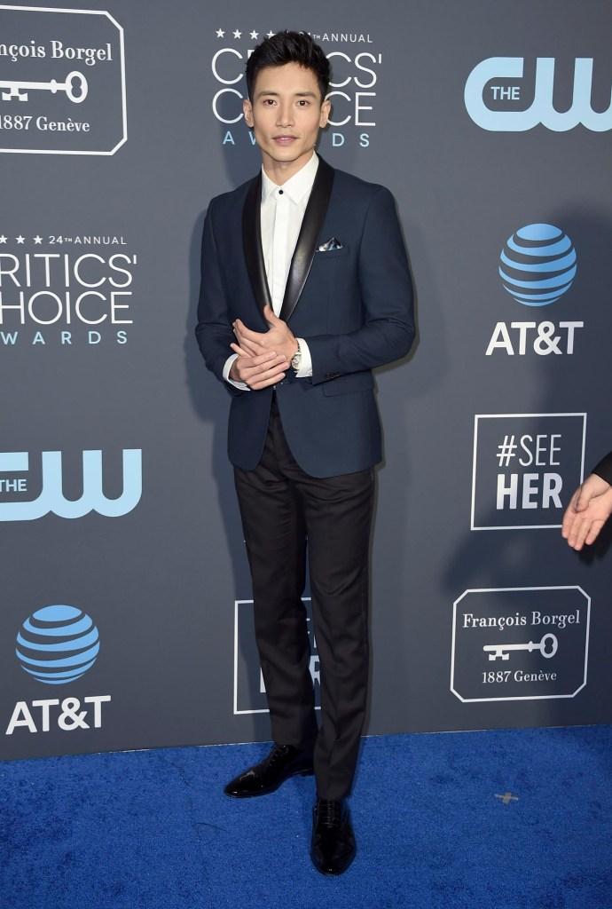 Manny Jacinto impecable con esmoquin sin corbata ni moño. Una opción formal para hombres bicolor en negro y azul noche. Saco azul con solapa de cuero negra, pantalón negro y zapatos acharolados negro. El detalle chic, el único botón negro de la camisa blanca