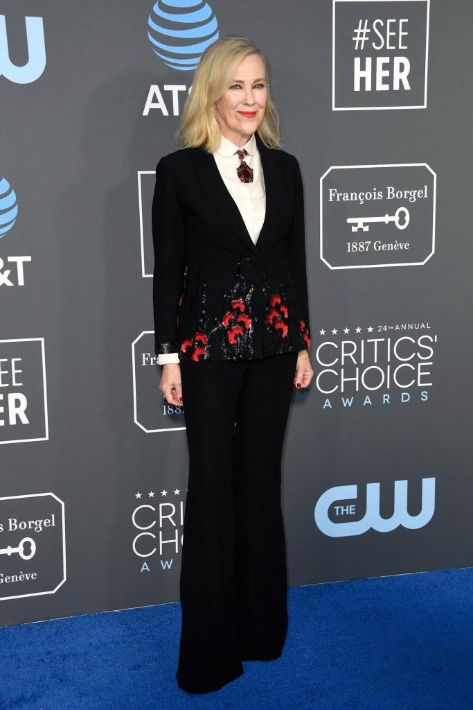 Catherine O'Hara apostó al traje masculino para los Critic's Choice Awards 2019. Pantalón oxford, y saco negro íntegramente brodado con flores y camisa blanca con detalle de colgante en el cuello