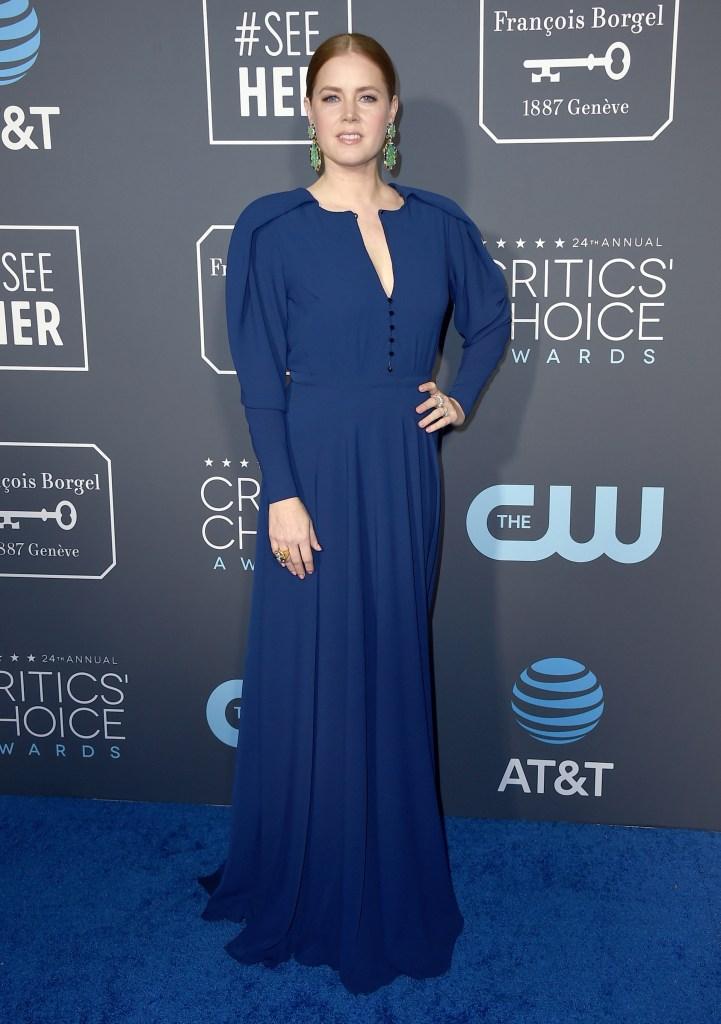 Amy Adams, mangas globo, corte en la cintura y escote V abotonado. Un diseño en azul noche acompañado por unos llamativos aros con esmeraldas y anillos dorados