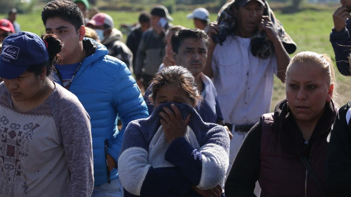 Familiares esperan información en la zona donde expertos forenses trabajan tras la explosión de una toma clandestina en Tlahuililpan, Hidalgo. (Foto: EFE)