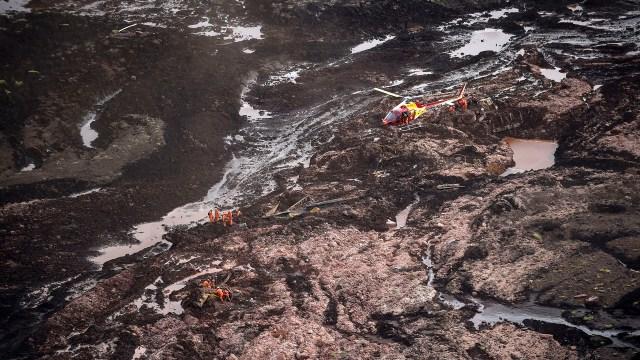 Un helicóptero de bomberos sobrevuela el área mientras se desarrollan las tareas de rescate (Photo by Douglas Magno / AFP)