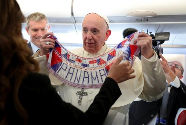 El Papa Francisco sostiene una pancarta de Panamá cuando se encuentra con periodistas a bordo de un avión que los lleva a la ciudad de Panamá, 23 de enero de 2019.