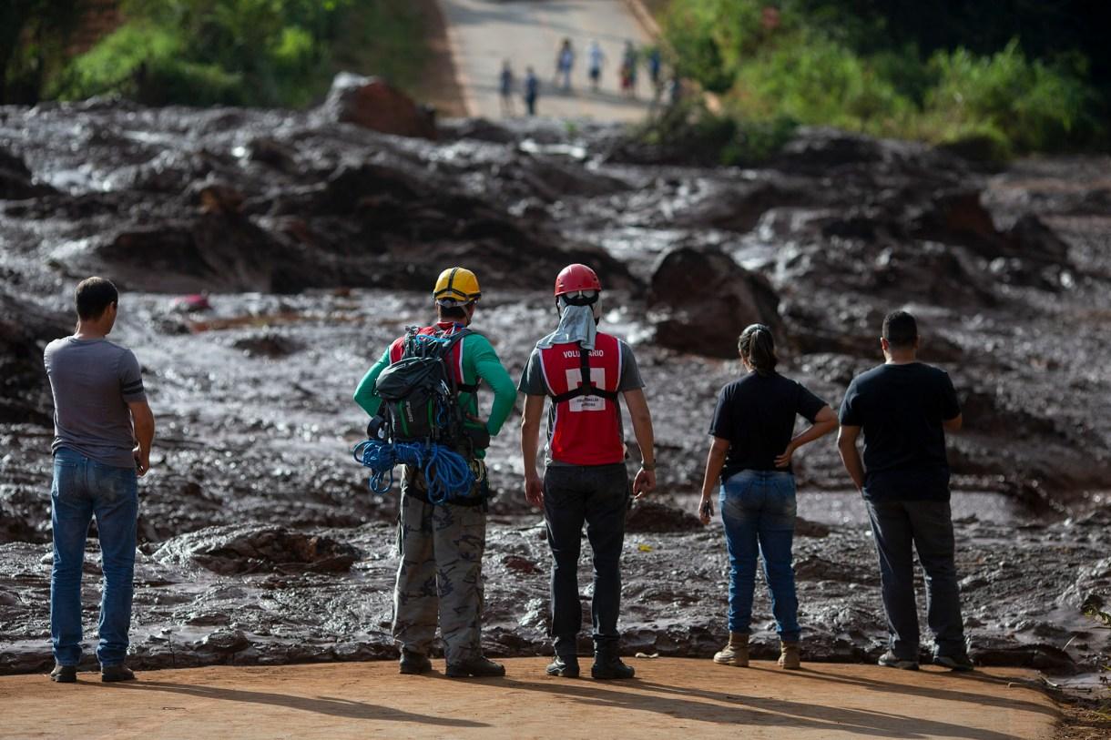Rescatistas observan los residuos liberados por el colapso del dique en Minas Gerais (AFP)