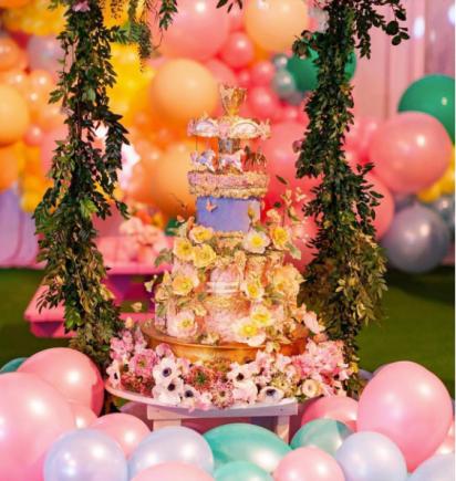 El espectacular pastel de cumpleaños: cuatro pisos, cubierto por flores, en colores pastel y con un carrusel móvil como topping.