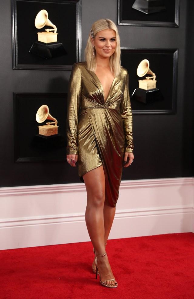 Tanya Rad con vestido asimétrico en color dorado drapeado, escote V y mangas largas. Completó el look con sandalias, anilos, aros y los accesorios it del momento: las hebillas de los noventa