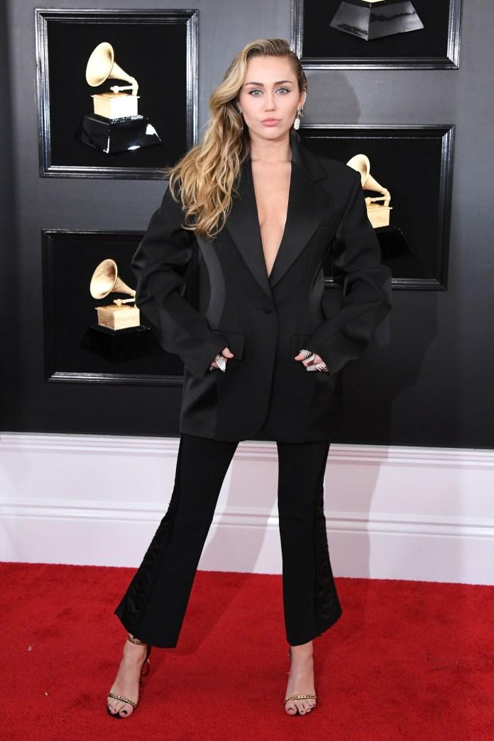 Miley Cyrus sorprendió con su outfit en la red carpet de los Grammy. Un saco oversized con pantalón semi oxford. En sus pies, sandalias doradas y negras. Completó su look con maxi anillos plateados y aros de brillantes