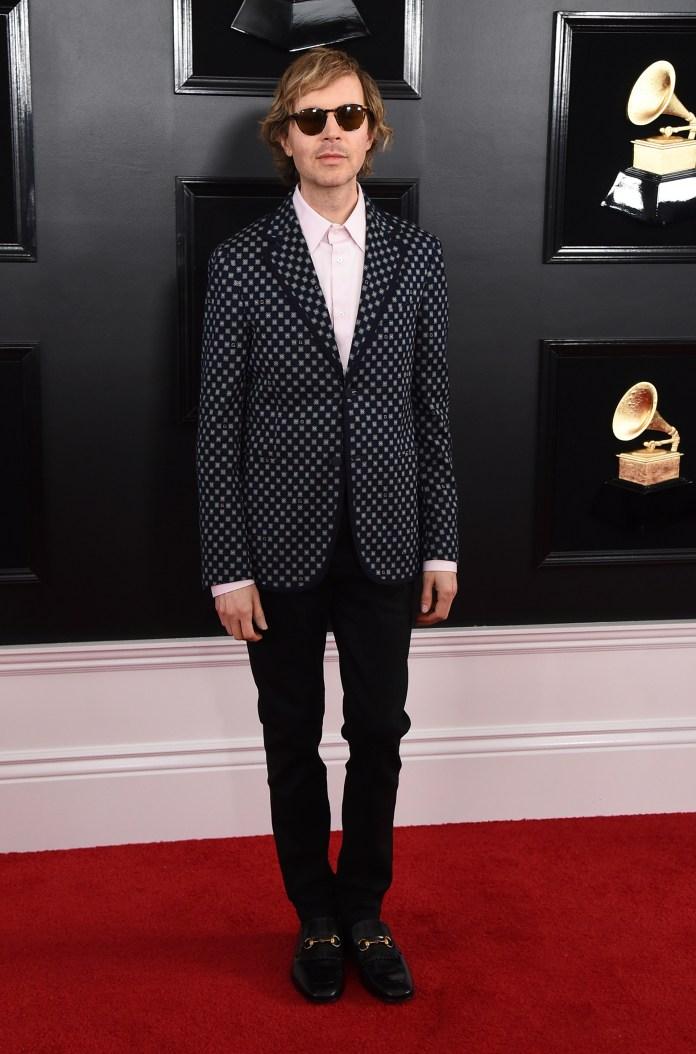 Beck sorprendió con su saco cuadrillé y camisa rosada. Lo completó con un clásico pantalón negro y mocasines de cuero negro