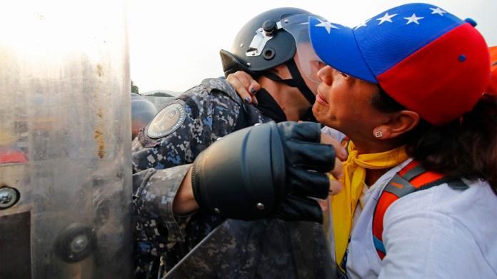 Una mujer besa a un guardia nacional que impide el paso de venezolanos a la frontera con Colombia donde recibirán ayuda humanitaria (AFP)