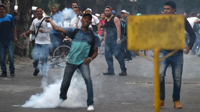 Los venezolanos se enfrentan a guardias nacionales en la ciudad fronteriza de Ureña luego de que el gobierno de Maduro ordenara cerrar temporalmente la frontera con Colombia este 23 de febrero (AFP)
