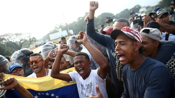 Los partidarios de la oposición venezolana exigen cruzar la línea fronteriza entre Colombia y Venezuela en el puente Simón Bolívar cuando las fuerzas de seguridad de Venezuela están en la línea fronteriza bloqueando su camino en las afueras de Cúcuta (Reuters)