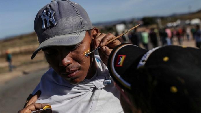Un venezolano se hace pintar la cara con la bandera nacional venezolana en la frontera (AP)