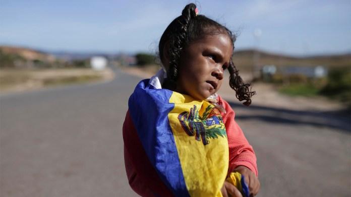 Una niña envuelta en una bandera nacional venezolana en la frontera en Pacaraima, estado de Roraima, Brasil, espera que le llegue la ayuda humanitaria (AP)