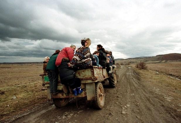 Albanos tratan de mantenerse en un camión al huir de Pantina, a 30 kilómetros de la capital