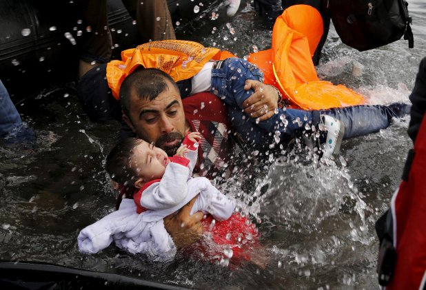 Un refugiado sirio lucha por mantener a flote a sus hijos al bajar de una embarcación en la isla griega de Lesbos