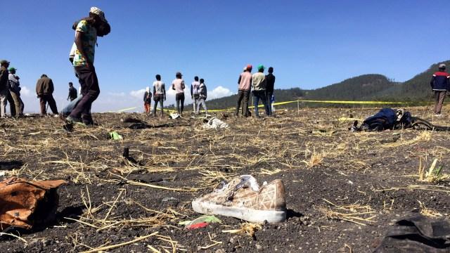 Habitantes de la zona caminan entre los restos del avión y pertenencias de las víctimas