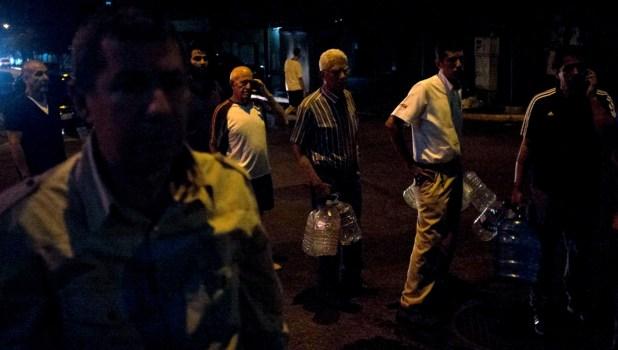 Ciudadanos forman filas para conseguir agua (AFP)