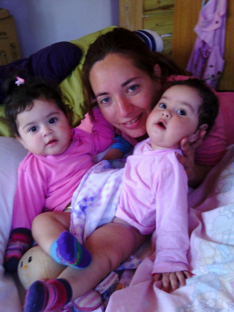 Las siamesas con su mamá. Paula lleva sus nombres tatuados en un antebrazo