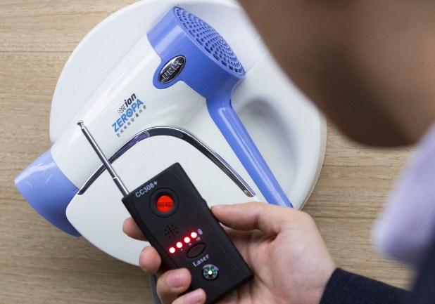 Un policía usa un detector de cámaras ante un dispositivo oculto en un secador de pelo (AFP)