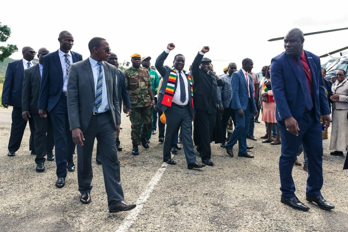 El presidente zimbabuense Emmerson Mnangagwa (L) saluda a partidarios con su vicepresidente Constantino Chiwenga (R) a su llegada a Mutare, provincia de Manicaland, antes de recorrer las áreas devastadas por el ciclón Idai en Chimanimani, el 19 de marzo. (Photo by Jekesai NJIKIZANA / AFP)