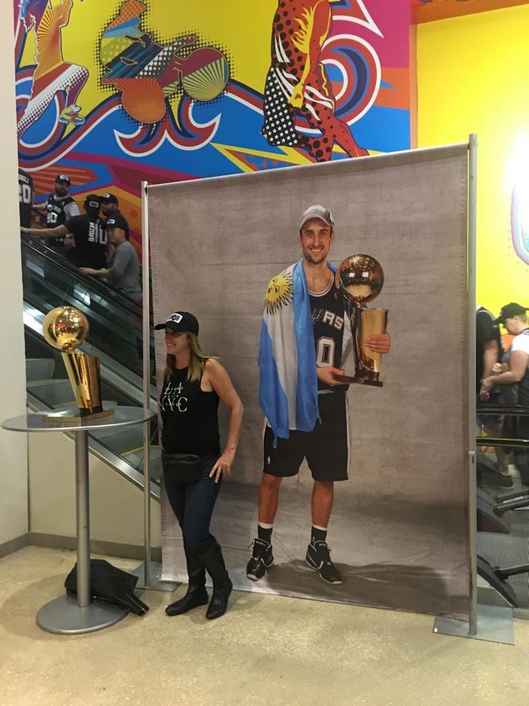 """Los fanáticos de """"Manu"""" Ginóbili se toman fotografías junto al trofeo de campeón de la NBA y el afiche del bahiense detrás"""