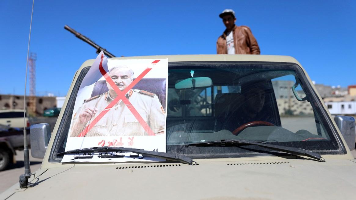Un vehículo militar de miembros de milicias leales al gobierno en Trípoli, con una foto tachada de Haftar (Reuters)