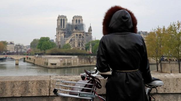 Una mujer mira a la Catedral de Notre Dame a la mañana siguiente del devastador incendio. (Reuters)
