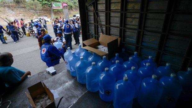 Bidones de agua que la Cruz Roja comenzó a repartir en Venezuela (AFP)